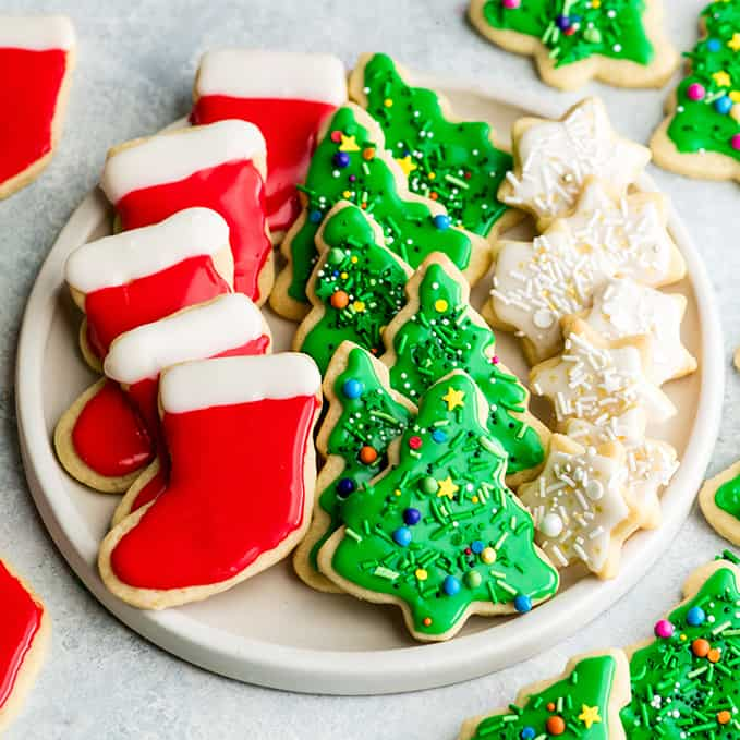 overhead view of a white, round plate with three rows of sugar cookies on it. The left row is five red and white stockings, the middle row is six green Christmas trees with sprinkles and the left row is seven small white stars with sprinkles.