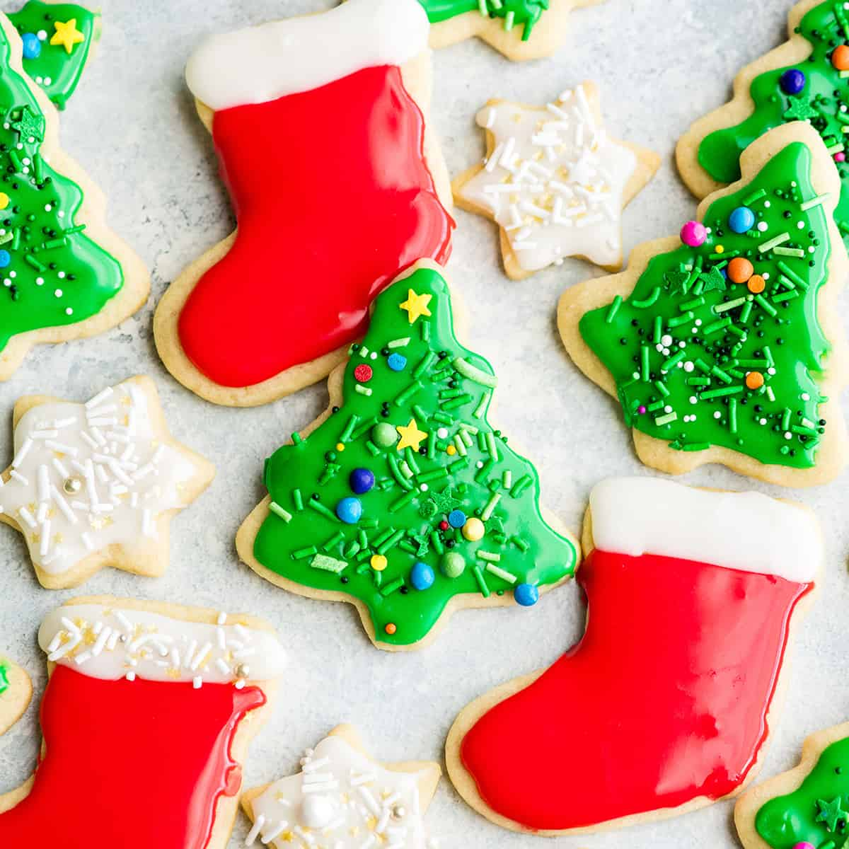 overhead view of Cut Out Sugar Cookies laying flat on a surface. Two green Christmas trees, two red and white stockings and two white stars with sprinkles.