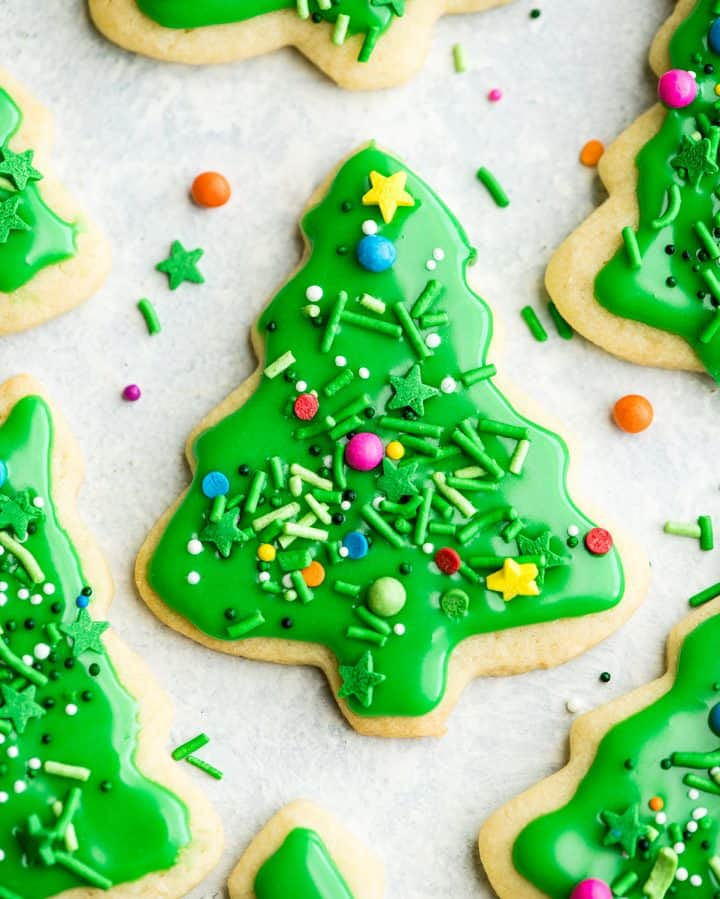 overhead view of a green Christmas tree sugar cookie with sprinkles