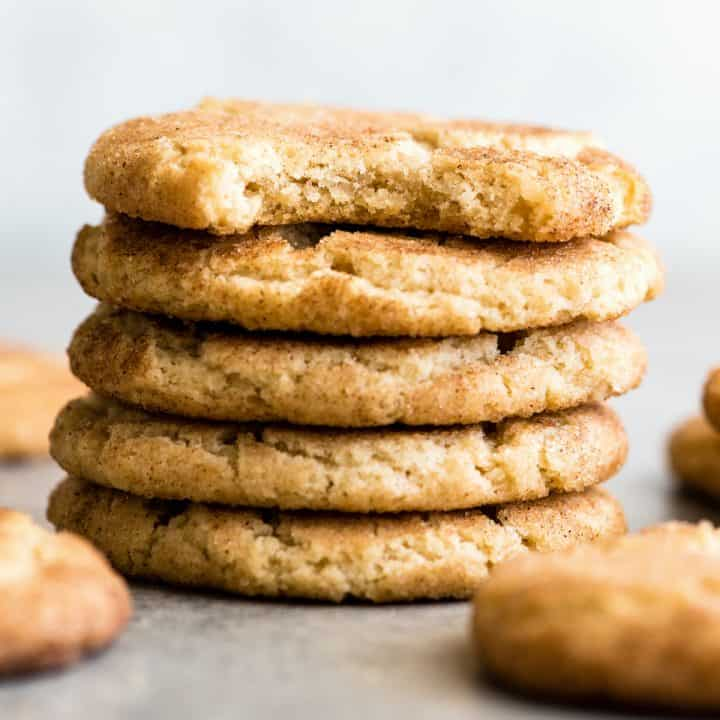 front view of a stack of 5 Snickerdoodle Cookies, the top one has a bite taken out of it