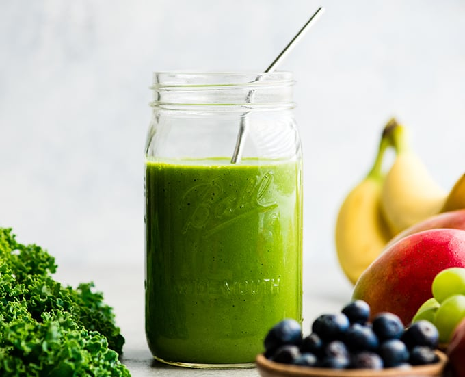 front view of a green smoothie in a large glass mason jar with a metal straw, surrounded with kale, blueberries, bananas, mangoes and green grapes