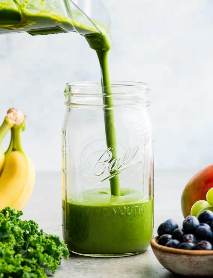 front view of a green smoothie being poured into a large glass mason jar, surrounded with kale, blueberries, bananas, mangoes and green grapes