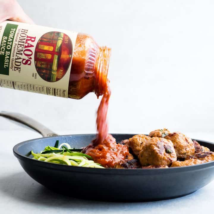 front view of pasta sauce being poured into a nonstick fry pan with zucchini noodles and Healthy Turkey Meatballs