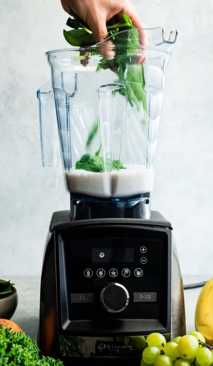 front view of a hand adding spinach to the almond milk in the container of a Vitamix A3500 blender to make this Green Smoothie Recipe