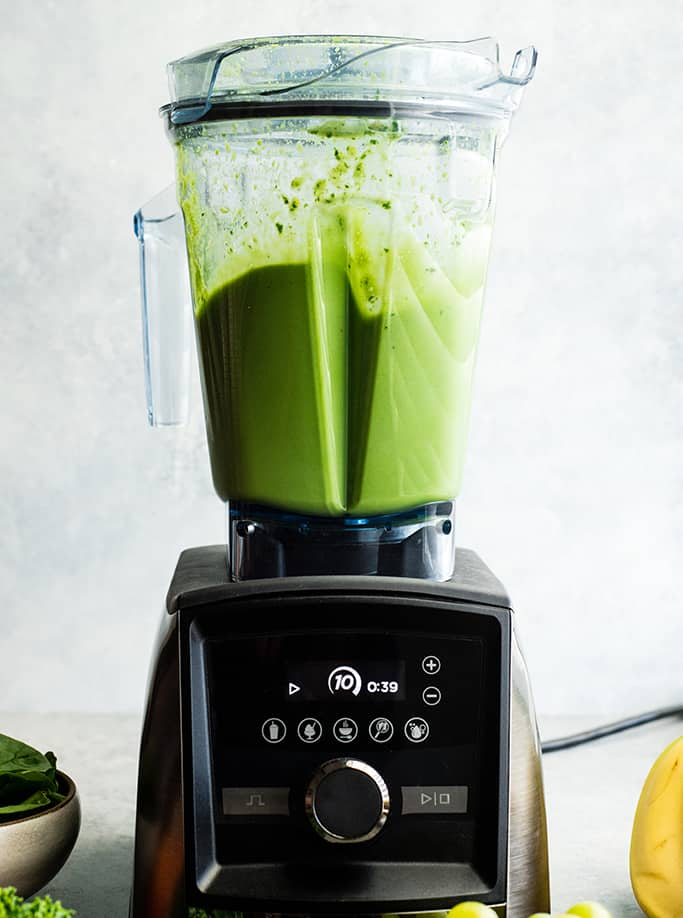 Front view of a Vitamix A3500 blender blending a green smoothie