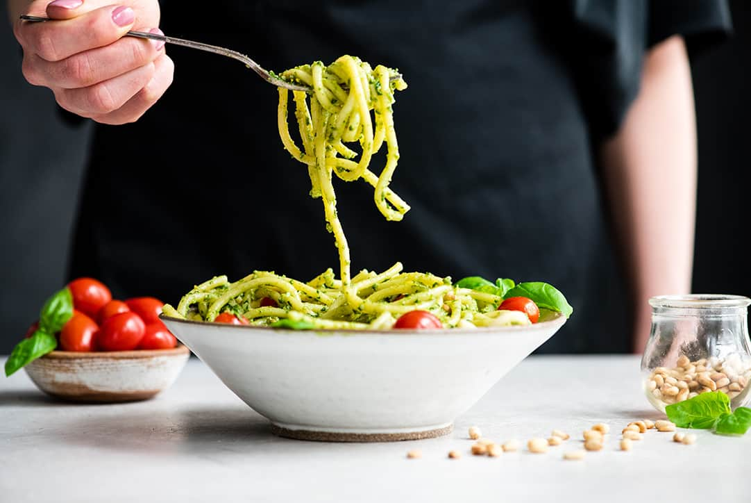 front view of a a hand holding a bite of pesto pasta over a bowl of Pesto Pasta with tomatoes, fresh basil and toasted pine nuts