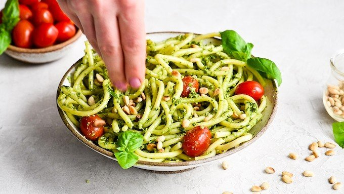 overhead/front view of a hand sprinkling pine nuts over a bowl of Pesto Pasta with tomatoes and fresh basil