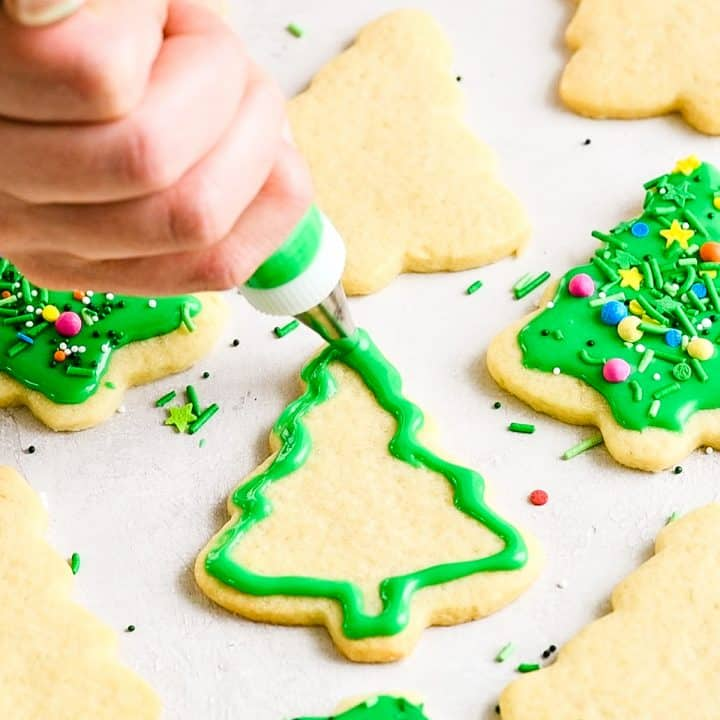 front view of a hand using a decorators bag to put green frosting on a tree-shaped sugar cookie