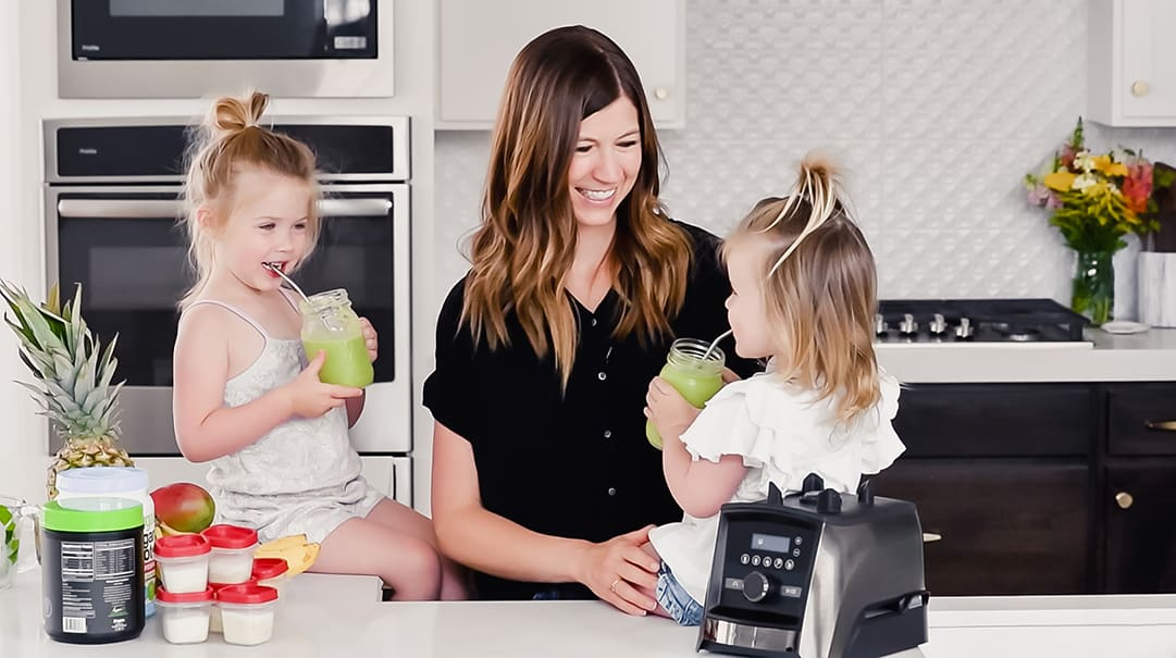 front view of a mom and her two kids sitting on the kitchen counter drinking green smoothies