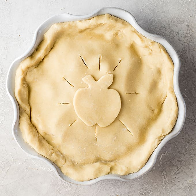 overhead view of an apple pie with the top crust on it before baking
