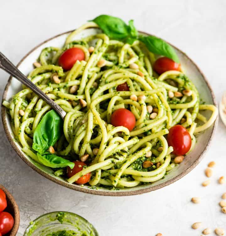 Overhead/front view of a bowl of Pesto Pasta with tomatoes, fresh basil and toasted pine nuts and a fork with a twirl of pasta on it