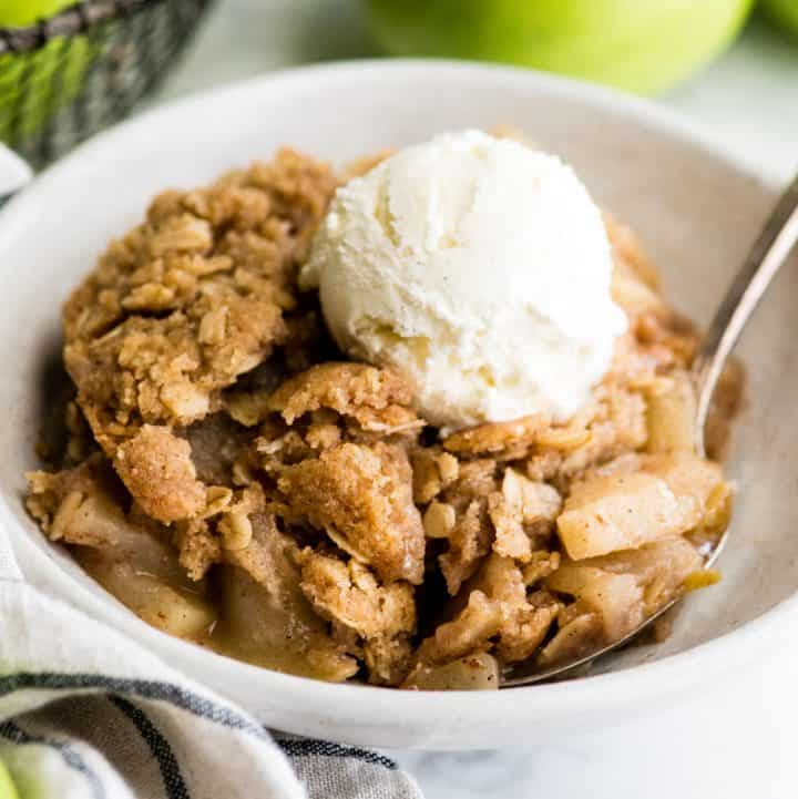 up close view of a bowl of apple crisp with ice cream on top
