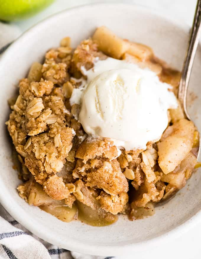 up close overhead view of a bowl of apple crisp with ice cream on top