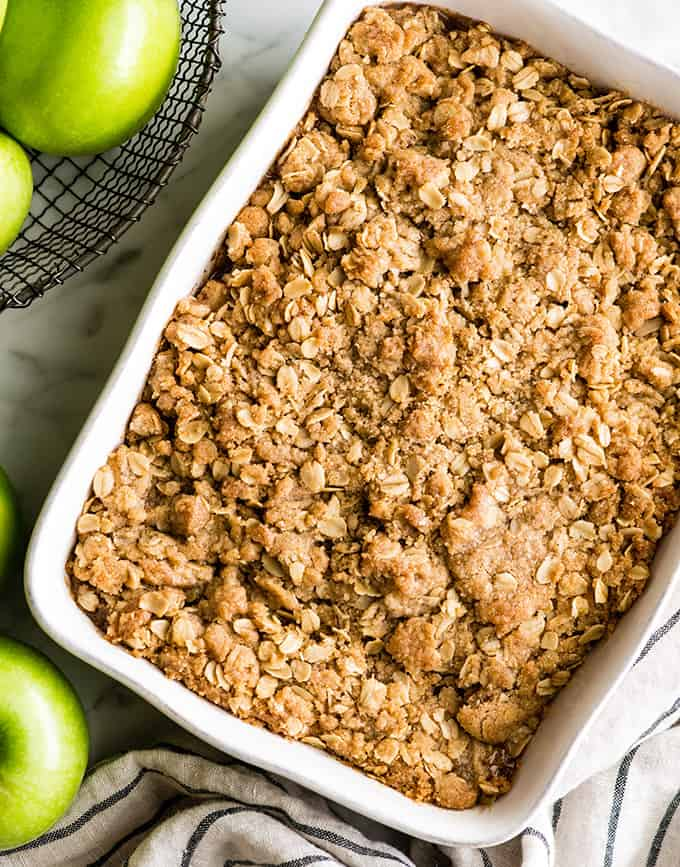overhead view of a apple crisp in a white rectangular baking dish after it has been baked