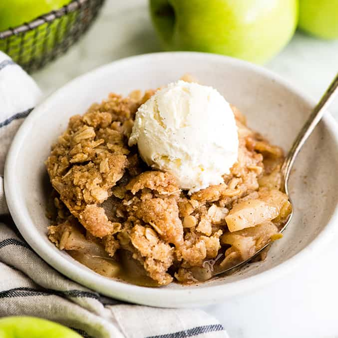 front view of a bowl of apple crisp with a scoop of ice cream on top