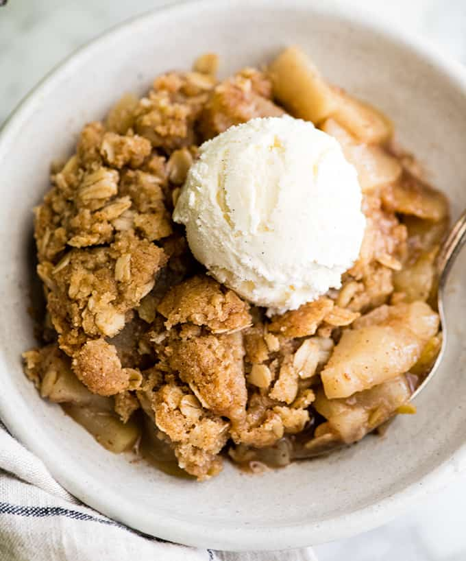 overhead view of apple crisp in a bowl with a scoop of ice cream on top
