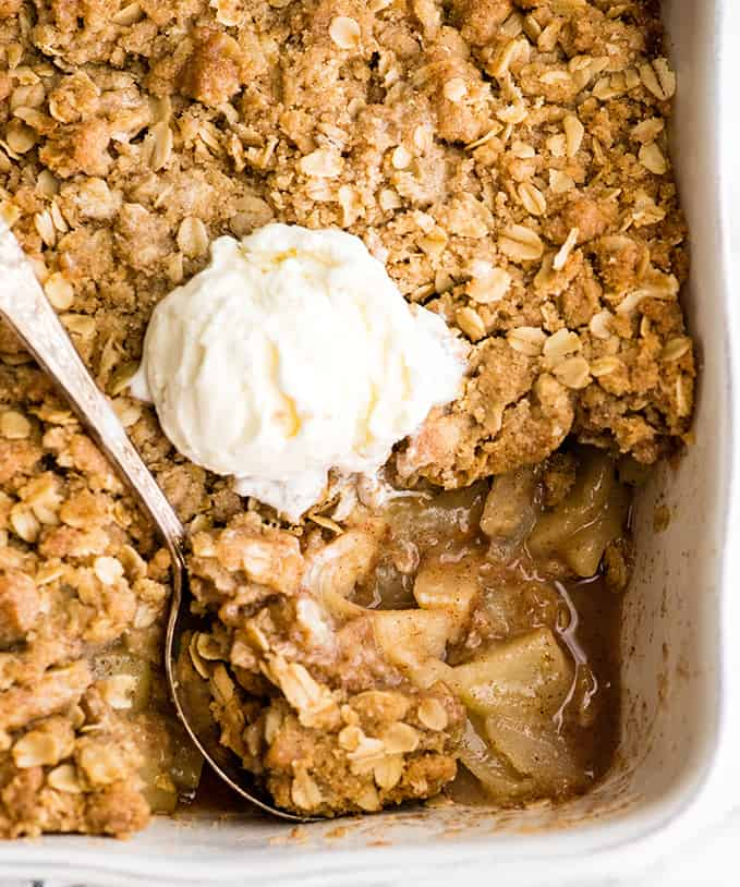 overhead view of apple crisp in a white baking dish after a scoop has been taken out, with a scoop of ice cream on top