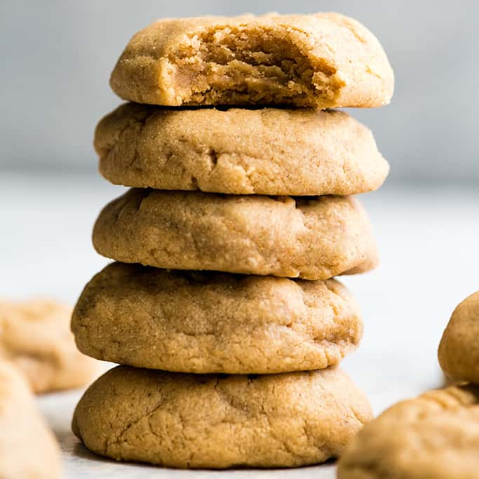 front view of a stack of 5 peanut butter cookies, the top has a bite taken out of it