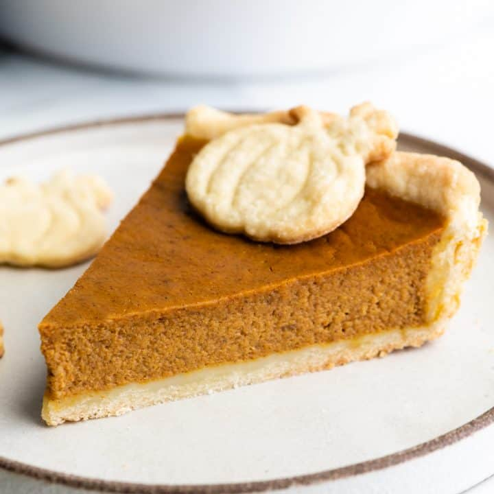front view of a slice of Pumpkin Pie on a plate with a pie crust pumpkin on top