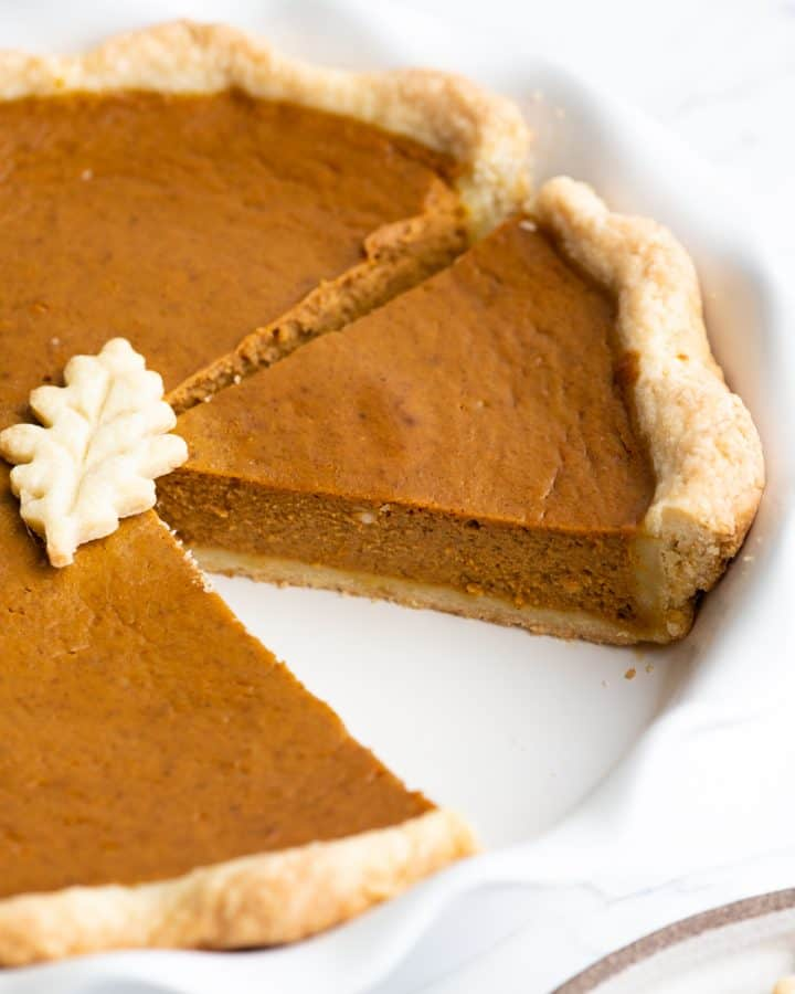 Pumpkin pie in a pie dish with a slice cut out