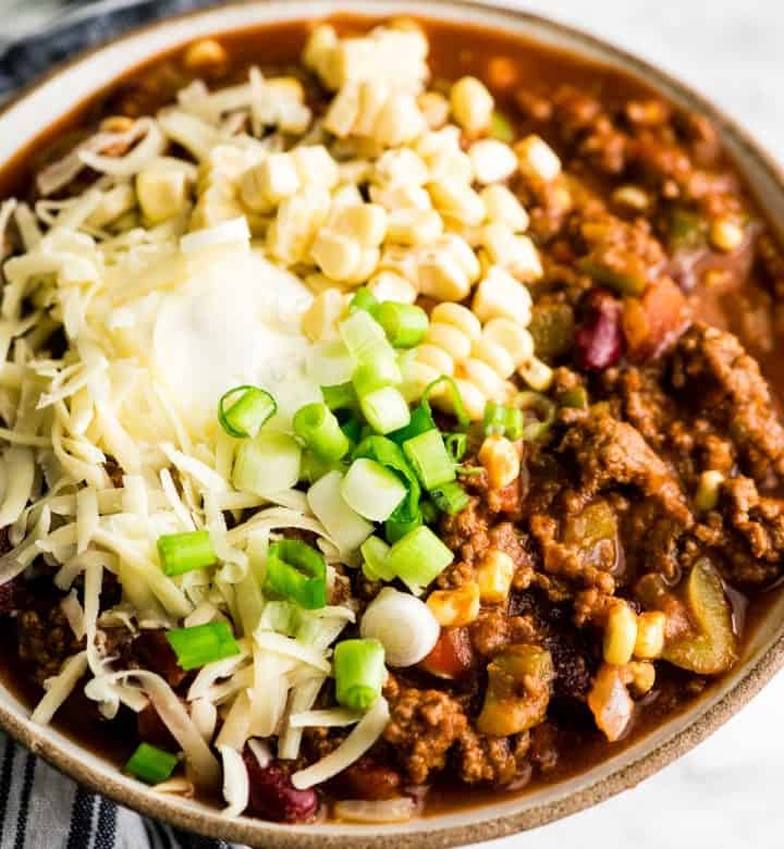 overhead view of Easy Chili Recipe in a bowl topped with sour cream, cheese, corn and green onions