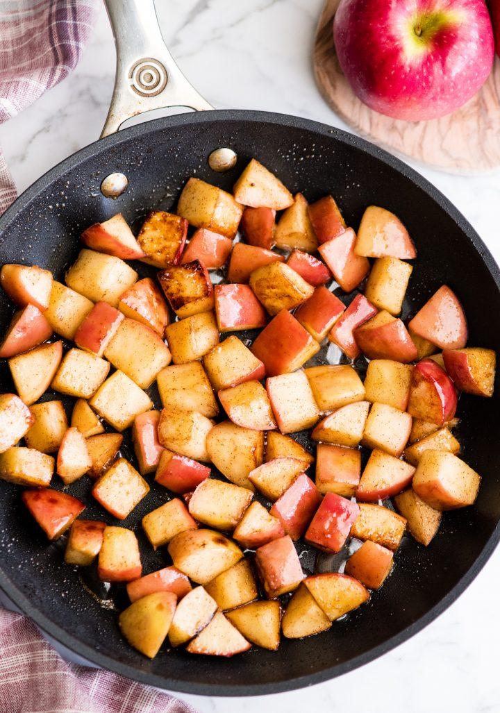 overhead view of sautéed cinnamon apples in a black nonstick fry pan