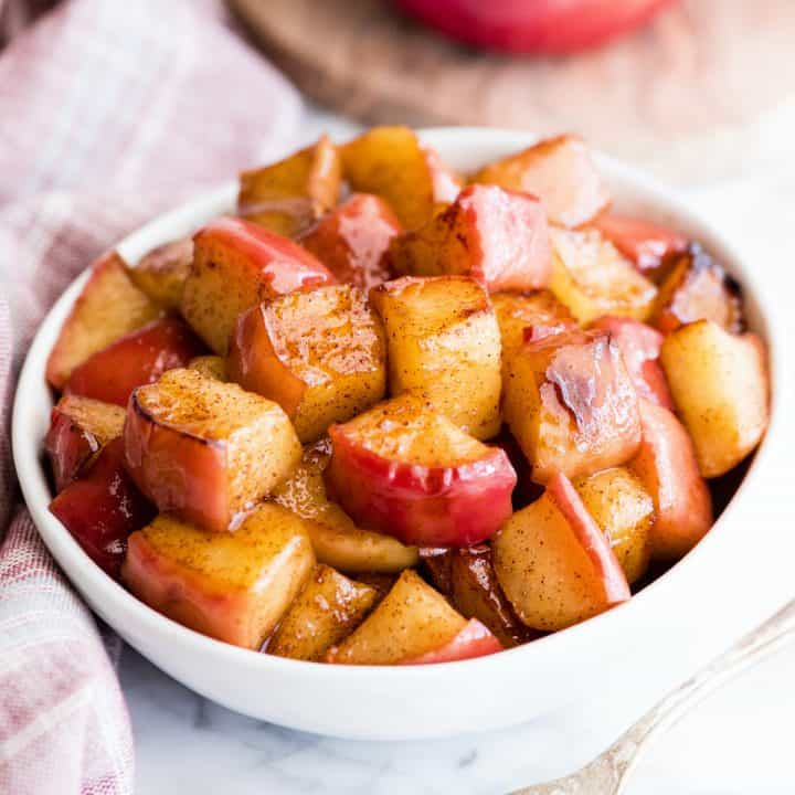 Overhead view of sautéed cinnamon apples in a white bowl