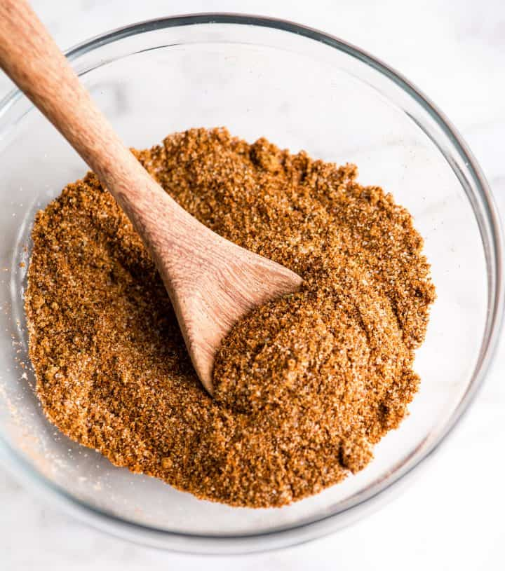 overhead view of a glass bowl of homemade chili seasoning with a wooden spoon