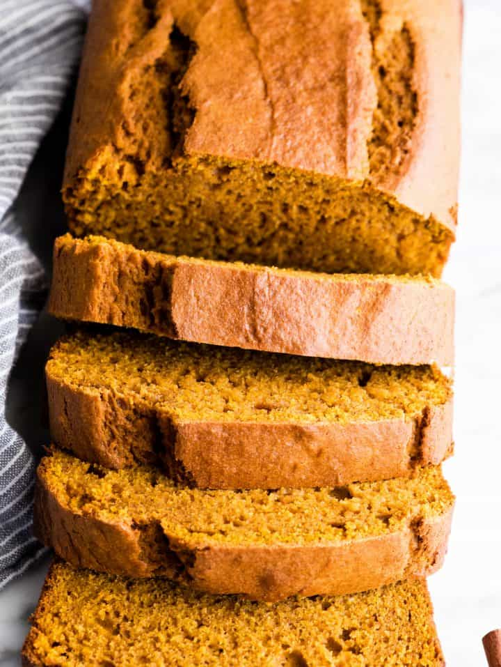 up close overhead view of a loaf of pumpkin bread with 4 slices cut out of it