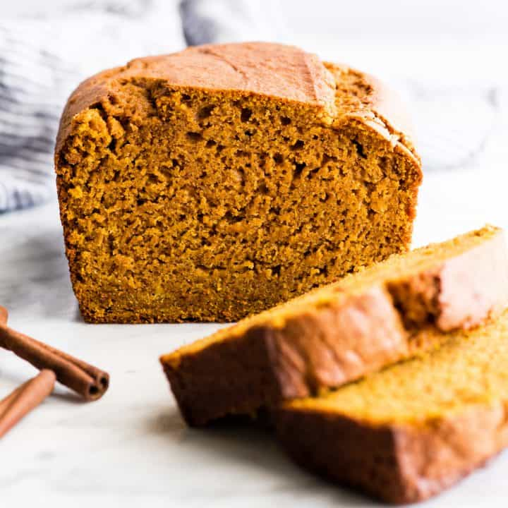 front view of a loaf of pumpkin bread with two slices cut out of it