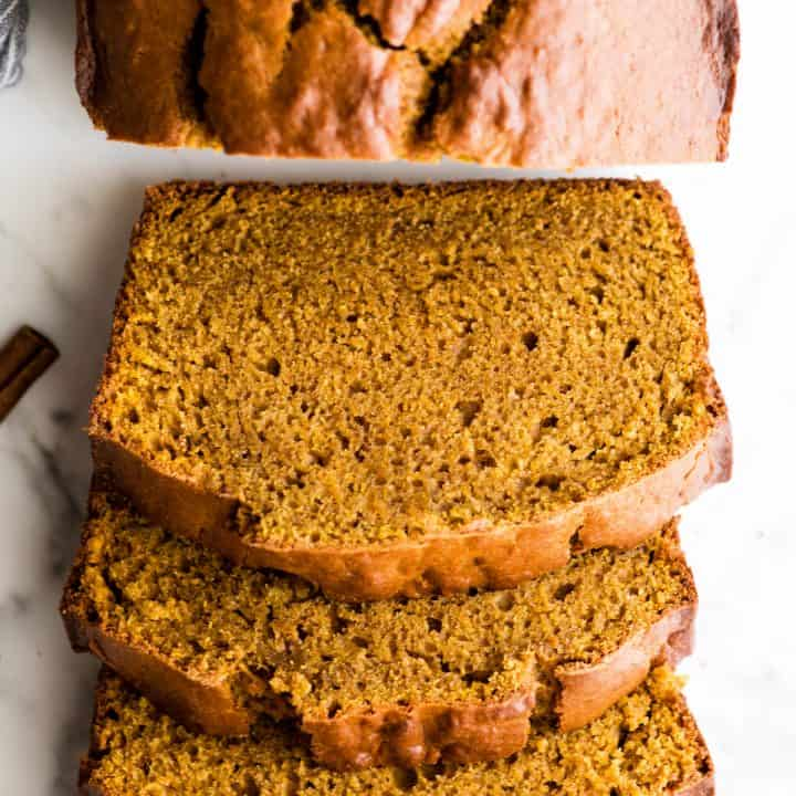 overhead view of a loaf of pumpkin bread with 4 slices cut