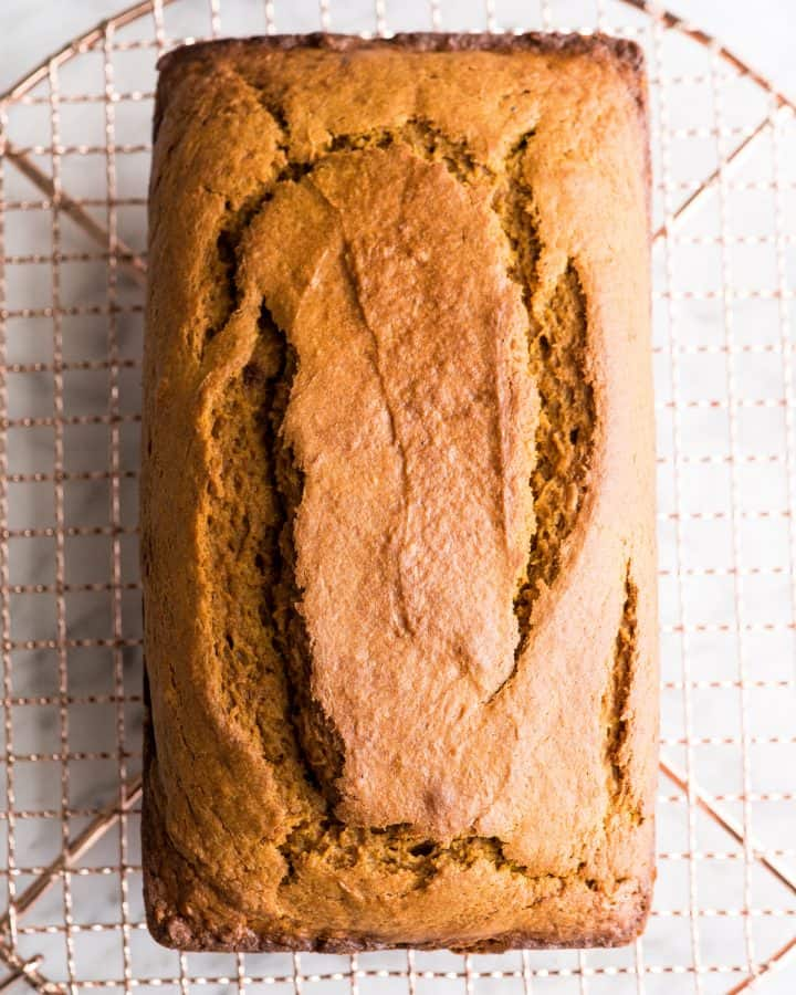 overhead view of a loaf of pumpkin bread cooling on a wire rack