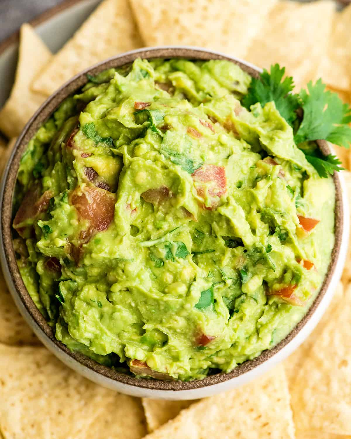 Overhead view of easy guacamole recipe in a bowl surrounded by chips