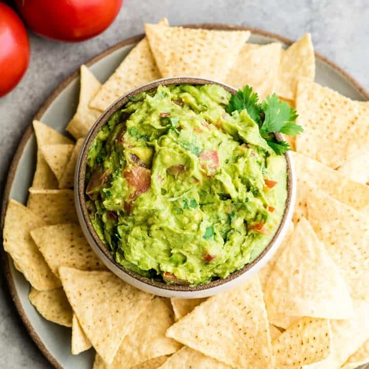 overhead view of a bowl of guacamole surrounded by chips