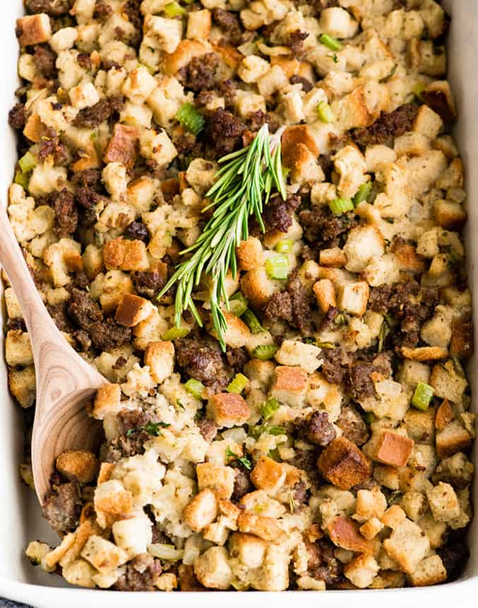 overhead view of sausage stuffing with rosemary on top and a spoon taking a scoop