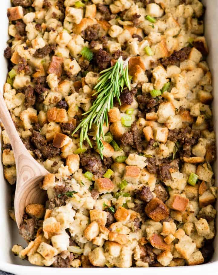 Overhead view of a baking dish of sausage stuffing with fresh rosemary on top and a spoon taking a scoop