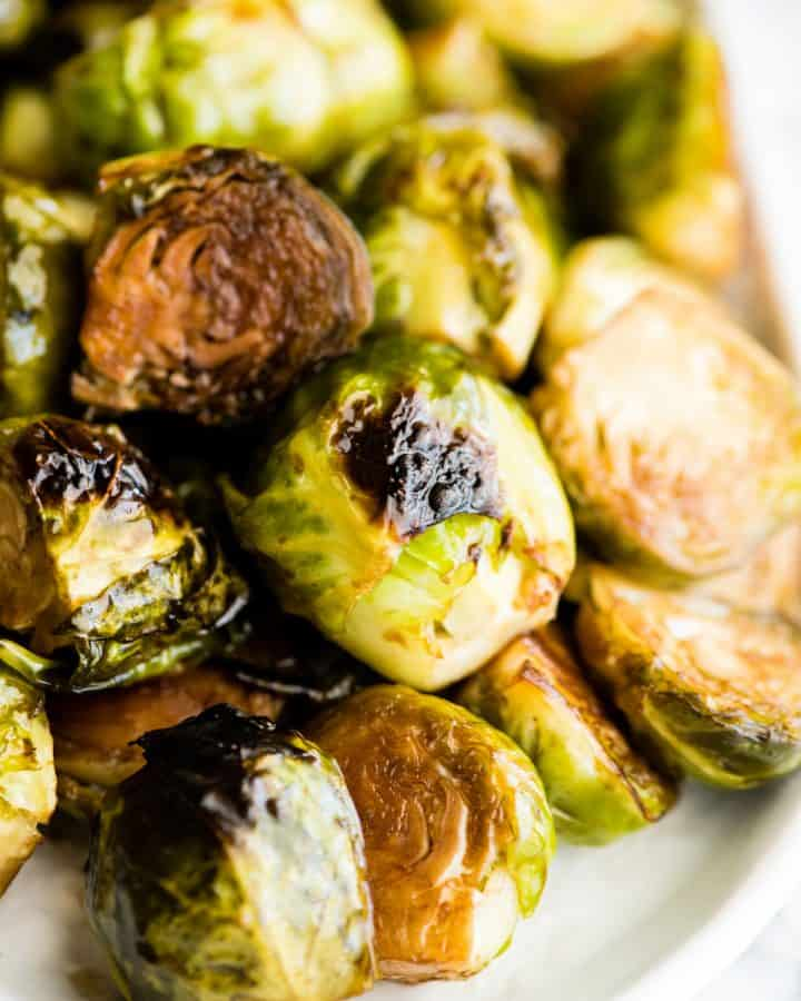 up close front view of balsamic roasted brussel sprouts on a serving dish