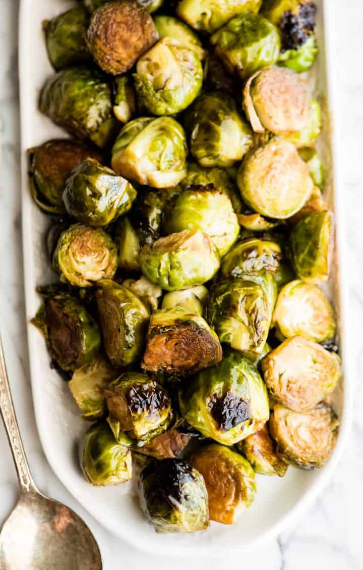 overhead view of balsamic roasted brussel sprouts on a serving dish
