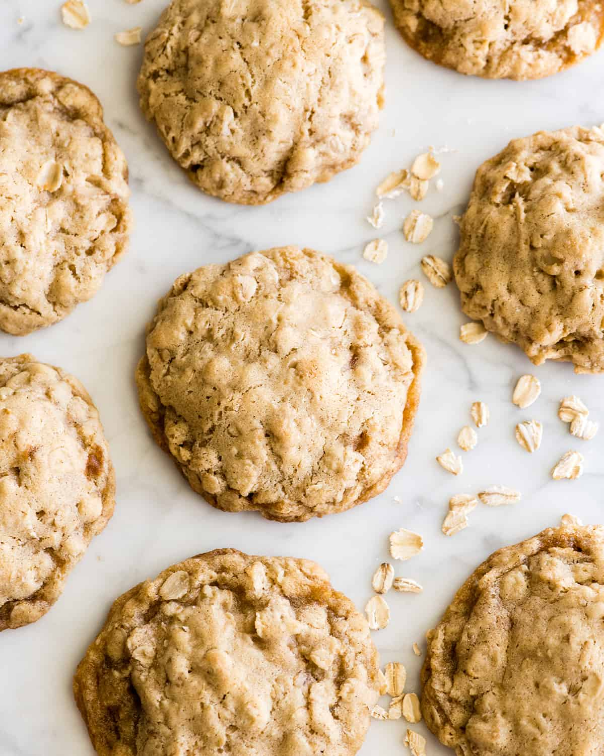 photo of seven oatmeal cookies on a white marble background