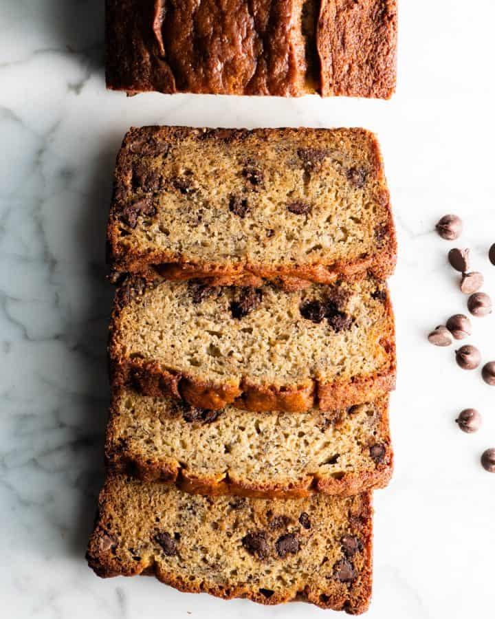 overhead view of a loaf of chocolate chip banana bread with 4 slices cut