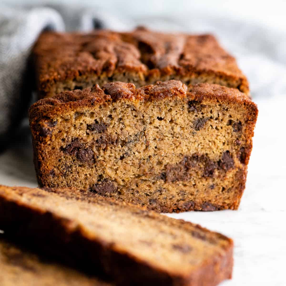 front view of a loaf of chocolate chip banana bread with slices cut out of it, some laying on the table one standing up in front of the loaf