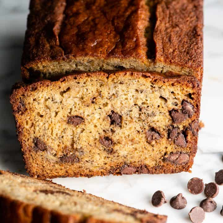 front view of a slice of banana chocolate chip bread resting on the loaf