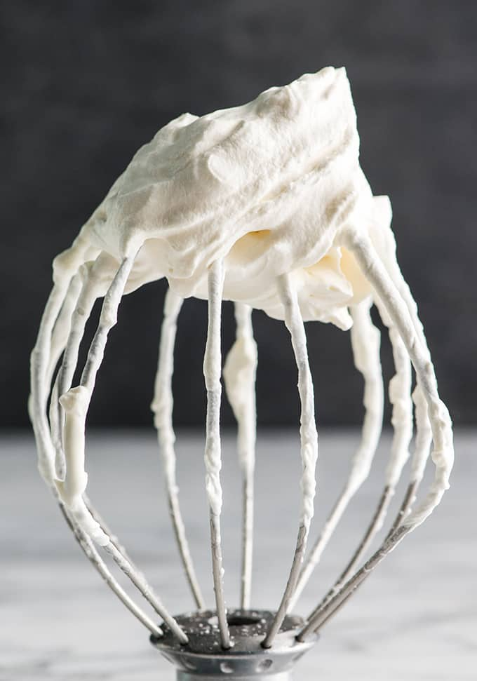 front view of a wire whisk with a stiff peak of homemade whipped cream on it