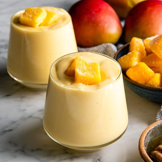 front view of two glasses filled with this mango smoothie recipe