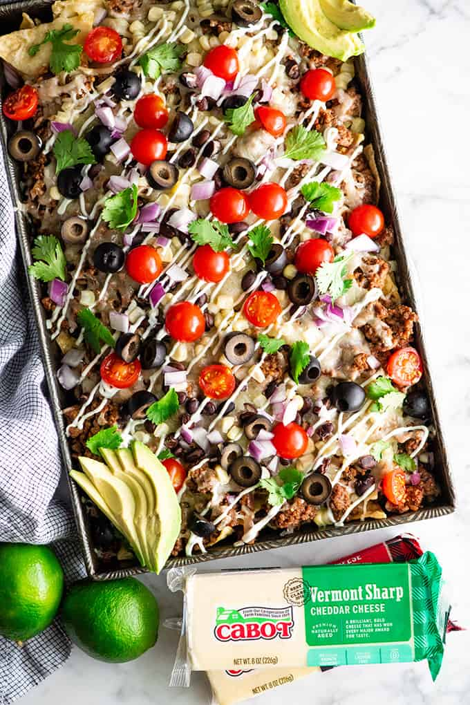 overhead view of best nachos recipe in a sheet pan with nacho toppings