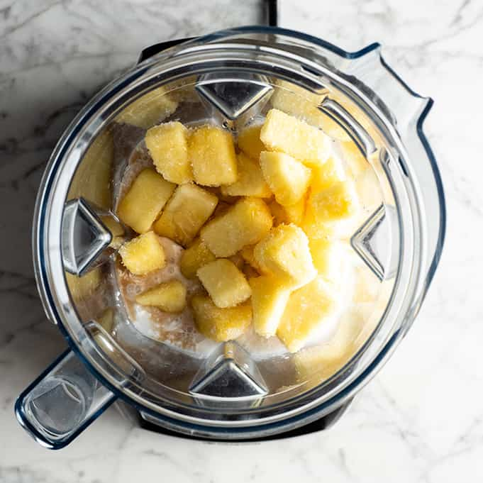overhead view of how to make a pineapple smoothie in a Vitamix blender