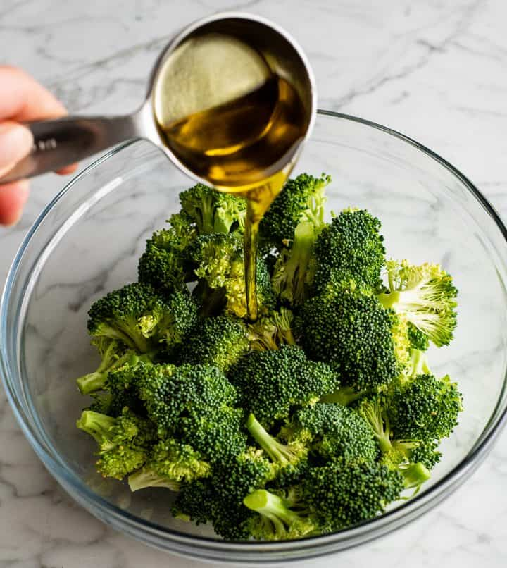 photo showing how to roast broccoli - pouring olive oil over broccoli