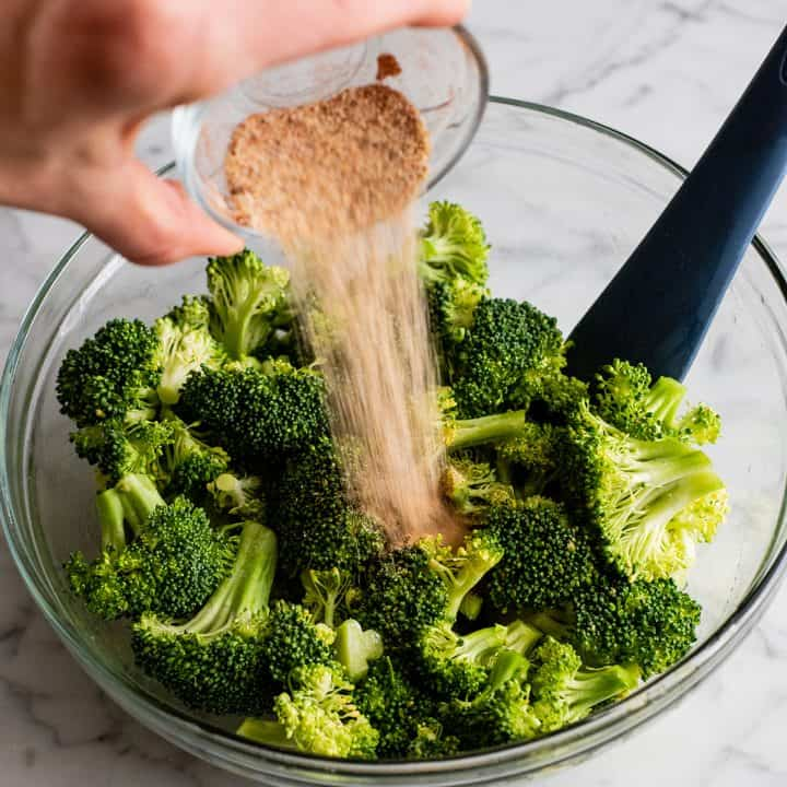 photo showing how to roast broccoli - pouring spice mixture onto oiled broccoli