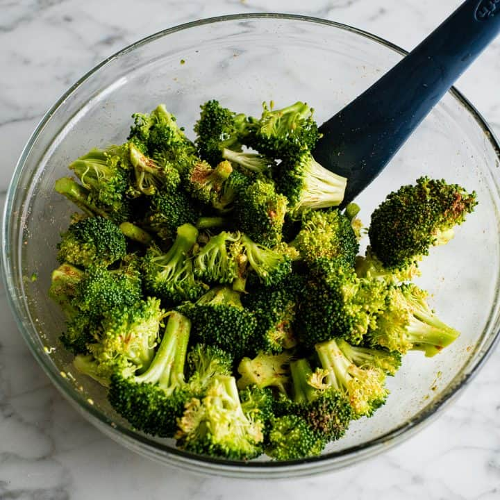 photo showing how to roast broccoli - stirring broccoli in a bowl