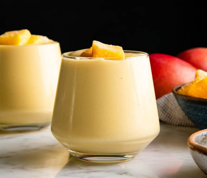 front view of two glasses filled with mango smoothie with frozen chunks of mango on top